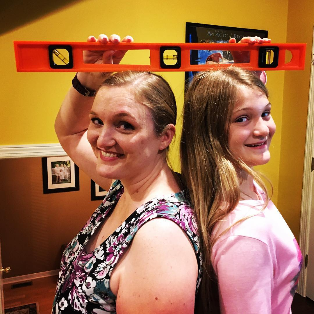 "It only took Kate 11 years and 8 months to pass her mama in height. We even used a level to prove it! Now less than 7"" left to catch daddy. #tallgirl #family #imstilltaller"